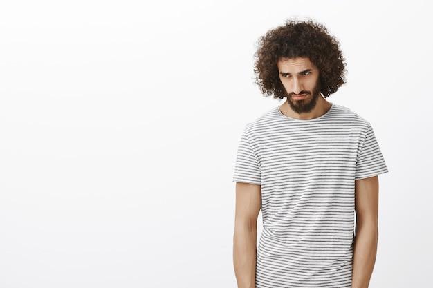 Modelo masculino bonito desesperado sombrio em uma camiseta listrada, cabeça inclinada e olhando para baixo com olhar triste. desistir depois de perder
