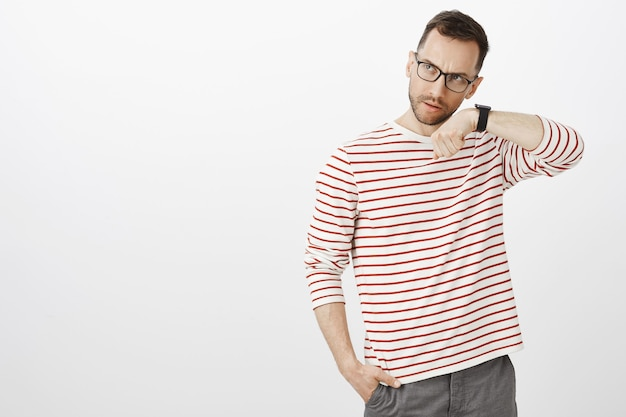 Modelo masculino bonito sério suspeito de óculos, segurando a mão perto da orelha e ouvindo o relógio, em pé sobre uma parede cinza, verificando se o dispositivo está funcionando corretamente