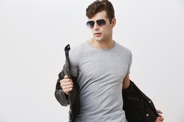 Modelo masculino caucasiano com recurso olhar posando dentro de casa. homem atraente bonito elegante com corte de cabelo da moda vestido com jaqueta de couro preta, usando óculos escuros.