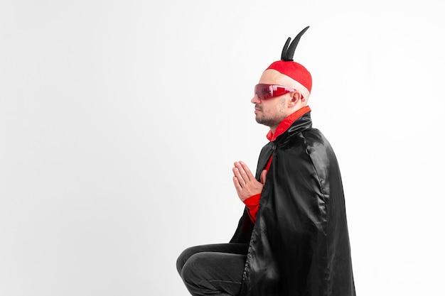 Modelo masculino caucasiano em traje vermelho preto de halloween e óculos escuros com chapéu e chifres orando sobre fundo branco.