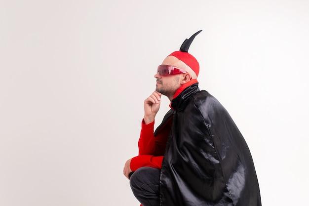 Modelo masculino caucasiano em traje vermelho preto de halloween e óculos escuros com chapéu e chifres posando sobre fundo branco.