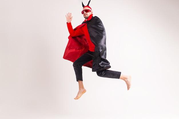 Modelo masculino caucasiano em traje vermelho preto de halloween e óculos escuros com chapéu e chifres, saltando sobre fundo branco.
