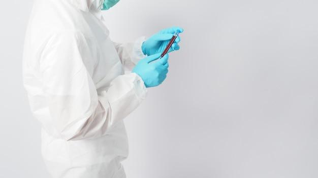 Modelo masculino com conjunto de ppe e mão com luva está segurando um tubo de ensaio de sangue em fundo branco.