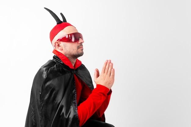 Modelo masculino com fantasia vermelha preta de halloween e óculos escuros com chapéu e chifres rezando