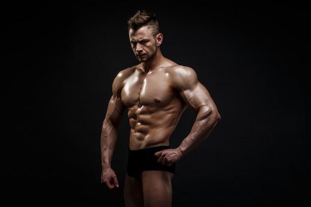 Modelo masculino considerável que levanta no estúdio na frente de um fundo preto.