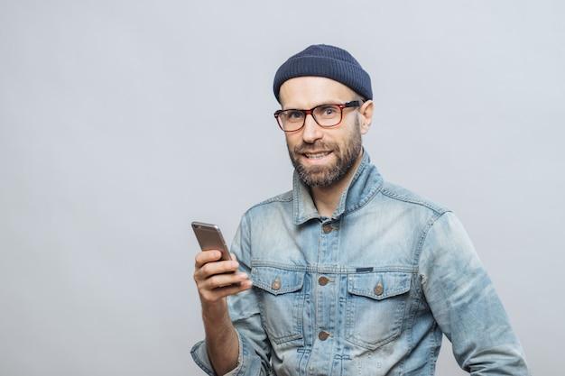 Modelo masculino de meia idade atraente com cerdas, vestida com roupas da moda, possui telefone inteligente