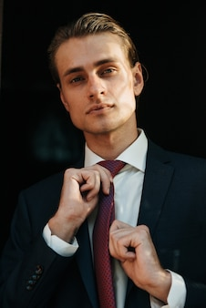 Modelo masculino de terno preto e gravata vermelha posa para publicidade de roupas masculinas. tiro para loja de roupas masculinas