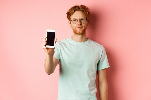 Modelo masculino desapontado com a testa franzida, mostrando a tela do smartphone, em pé sobre um fundo rosa