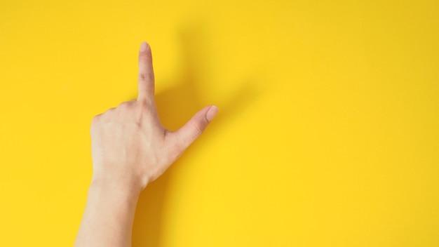 Modelo masculino é apontar o dedo para cima sinal de mão com a mão traseira em fundo amarelo.