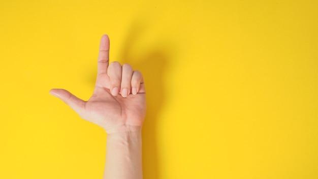Modelo masculino é apontar o dedo para cima sinal de mão com para a mão sobre fundo amarelo.