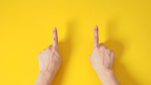 Modelo masculino é apontar o sinal de mão do dedo sobre fundo amarelo.