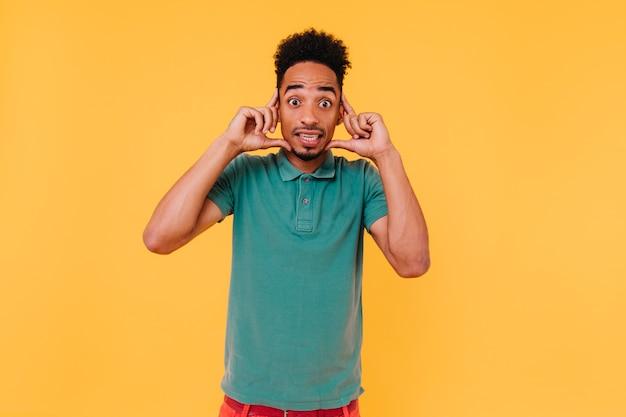 Modelo masculino engraçado de olhos escuros olhando com expressão de surpresa. retrato interior de cara bonito espantado com t-shirt verde.