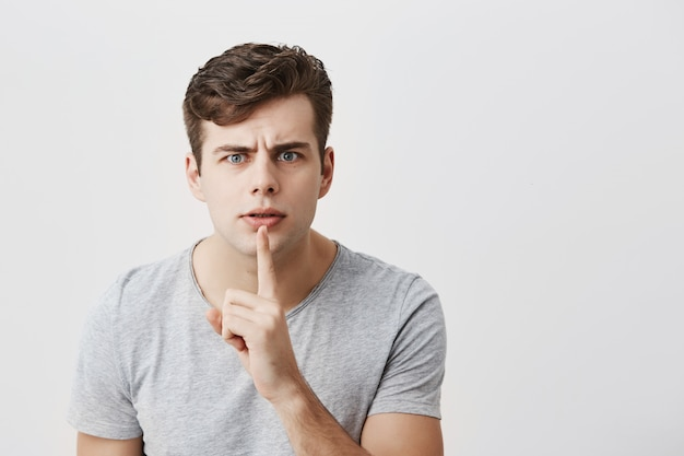Modelo masculino europeu em camiseta cinza, mantendo o dedo indicador nos lábios, franzindo a testa, pedindo para segurar a língua e manter informações confidenciais privadas. ultra secreto
