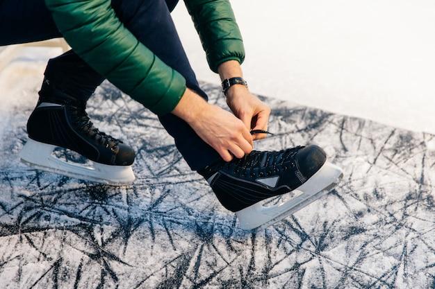 Modelo masculino irreconhecível estar no gelo coberto de neve, amarra patins, vai andar de skate com prazer