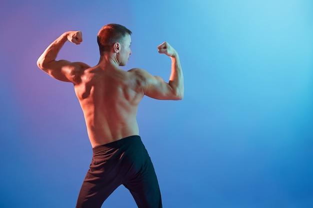 Modelo masculino jovem e em forma mostrando os músculos das costas
