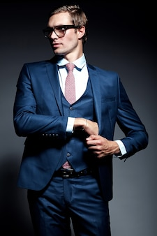 Modelo masculino jovem empresário bonito elegante de terno azul e óculos da moda, posando no estúdio