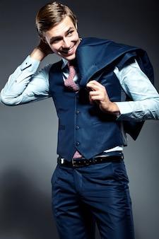 Modelo masculino jovem empresário bonito elegante terno azul posando no estúdio