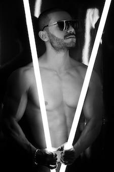 Modelo masculino nu na sombra com tristeza leve, olhando de cabeça