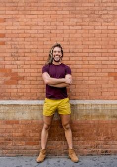 Modelo masculino posando com parede de tijolo