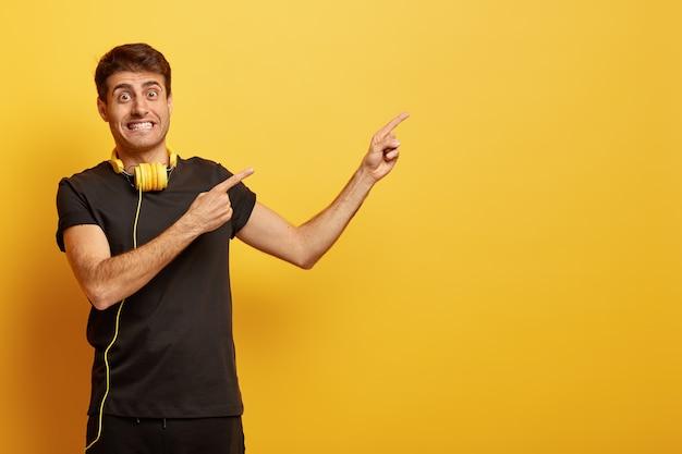 Modelo masculino positivo aperta os dentes, aponta para um espaço em branco para seu texto ou anúncio, usa fones de ouvido no pescoço