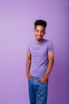 Modelo masculino refinado com cabelo encaracolado em pé com expressão de sorriso no rosto. tiro interno de jovem feliz de mãos dadas nos bolsos.