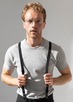 Modelo masculino segurando os suspensórios, vista frontal