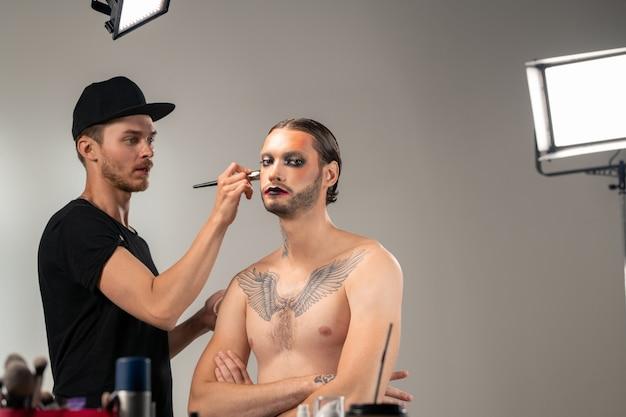 Modelo masculino sem camisa com maquiagem de palco cruzando os braços no peito e olhando para você enquanto jovem com pincel aplica pó facial