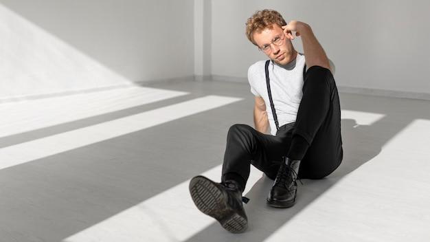 Modelo masculino sentado no chão, plano geral
