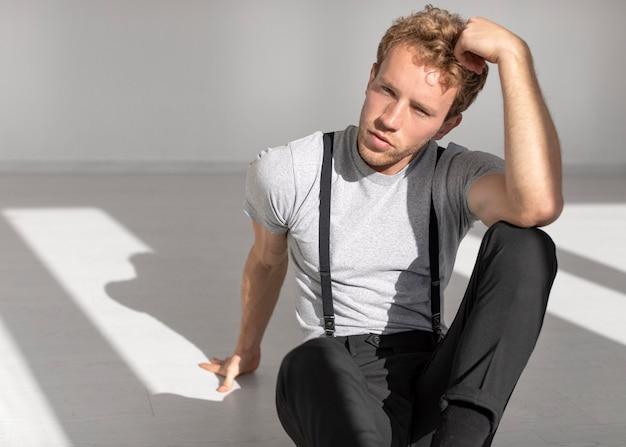 Modelo masculino sentado no chão, vista frontal