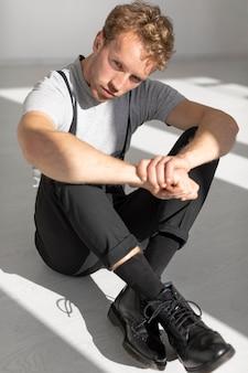 Modelo masculino sentado no chão