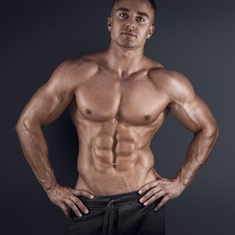 Modelo masculino sexy sem camisa posando contra um fundo escuro