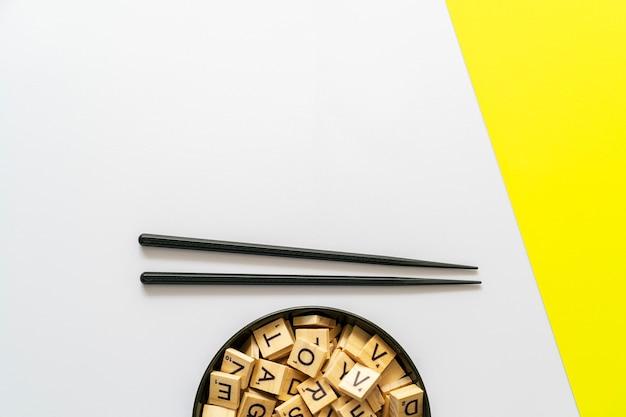 Modelo mínimo de fundo branco e amarelo com pauzinhos e uma tigela cheia de letras de madeira