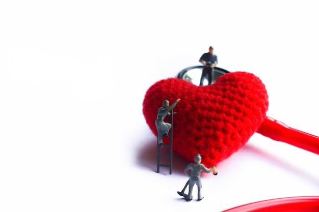 Modelo minúsculo cuidar modelo coração vermelho perto do estetoscópio vermelho