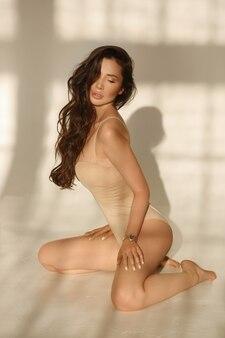 Modelo morena com lábios carnudos em macacão bege sentada no chão