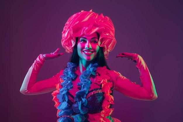 Modelo morena havaiana atraente na parede roxa do estúdio com luz de néon