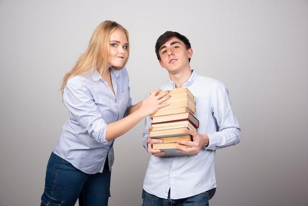 Modelo moreno carregando uma pilha de livros perto de uma mulher loira