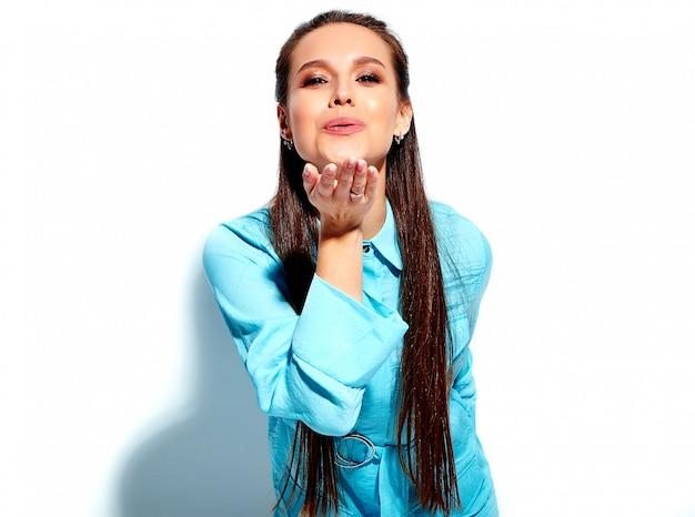Modelo moreno de sorriso caucasiano bonito da mulher no vestido à moda do verão azul brilhante isolado no fundo branco. dando um beijo