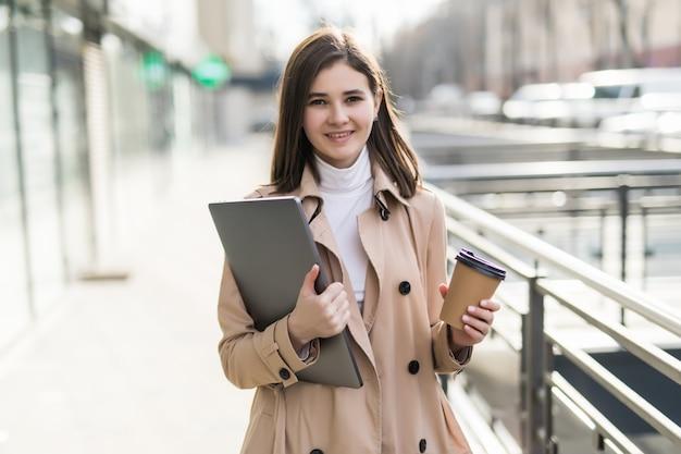 Modelo moreno em roupas casuais fica com o laptop ao ar livre