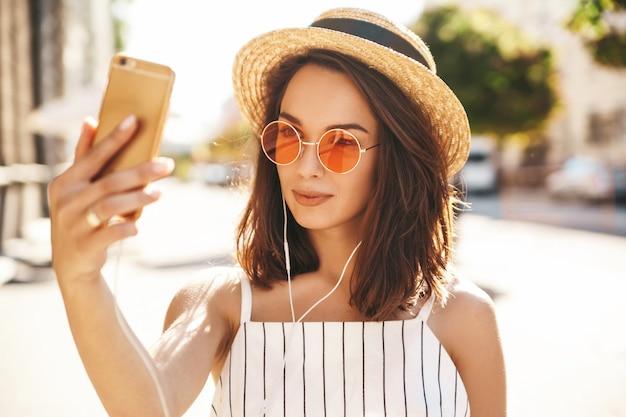 Modelo moreno em roupas de verão, posando na rua usando telefone celular