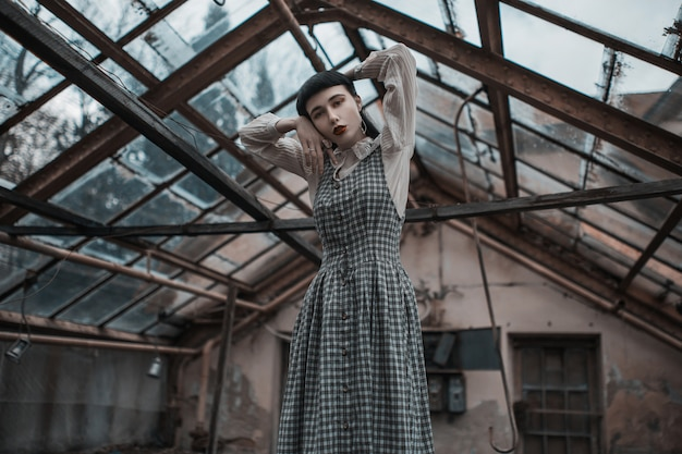 Modelo moreno gótico de vestido. moda vitoriana. modelo gótico em fundo grunge. misteriosa mulher morena com estrondo. modelo de vestido em fundo abandonado. roupas da moda. vampiro misterioso