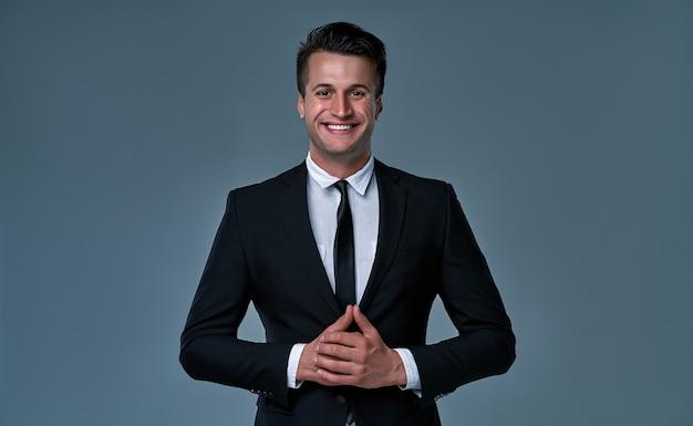 Modelo moreno jovem e bonito, vestindo terno preto e branco, sorrindo, posando no estúdio, isolado no fundo cinza. retrato de homem de negócios. copie o espaço. visualização horizontal.