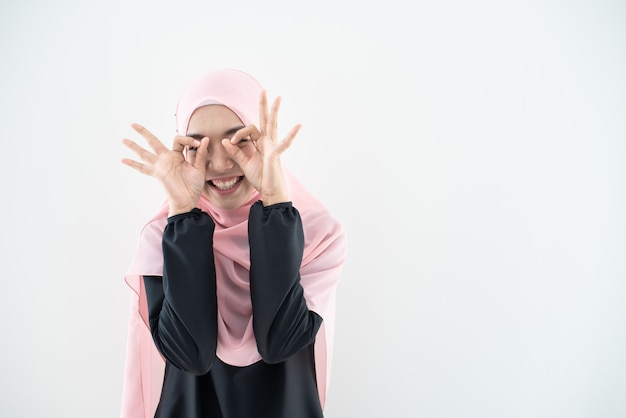 Modelo muçulmano fêmea bonito no kurung e no hijab modernos, um fato moderno do estilo de vida para as mulheres muçulmanas isoladas na parede branca. conceito de moda beleza e hijab. retrato de meio comprimento