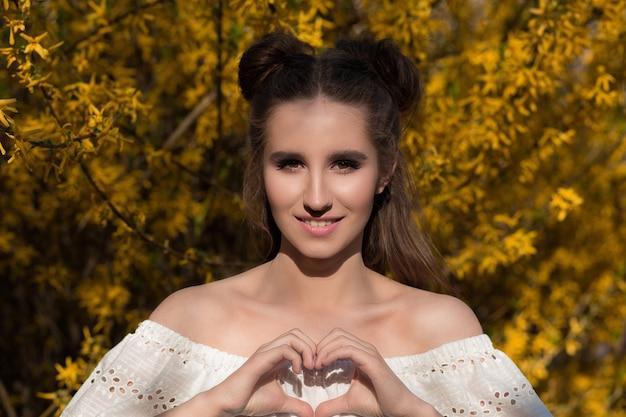 Modelo muito feliz posando perto de flores amarelas desabrochando e mostrando um gesto de coração
