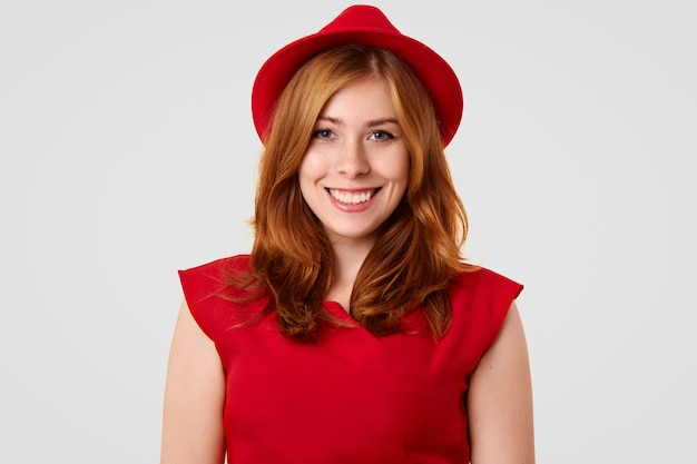 Modelo muito feminino com sorriso positivo, vestido com blusa e chapéu vermelho elegante, vai ter um encontro com o namorado