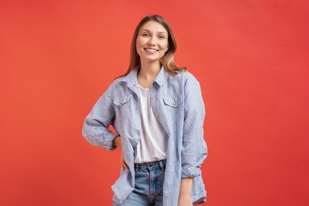 Modelo muito feminino, posando com uma expressão de rosto sorridente na parede vermelha