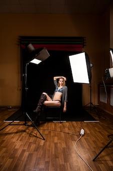 Modelo mulher com cueca em posição atraente na cadeira em luzes brilhantes