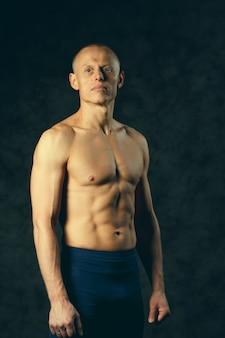 Modelo muscular esportes jovem em fundo escuro. retrato da moda de forte cara brutal com um penteado moderno e moderno. torso sexy. macho flexionando seus músculos. esporte treino musculação concep. toned