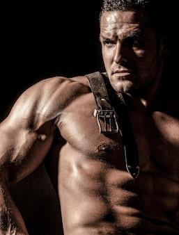 Modelo muscular esportes jovem em fundo escuro. retrato da moda do cara forte e brutal. cinto de couro, jeans. torso sexy. conceito de musculação de treino de esporte. corpo de homem sensual.