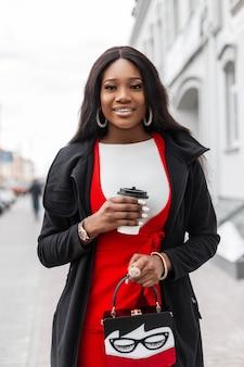 Modelo na moda jovem africana positiva num elegante terno vermelho na jaqueta com uma xícara de café anda perto de edifício vintage na cidade. alegre garota negra na moda com sorriso fofo gosta de beber e caminhar.