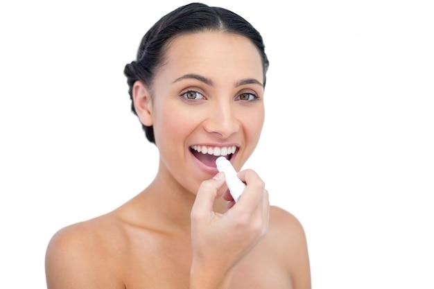 Modelo natural jovem entusiasta aplicando bálsamo para os lábios